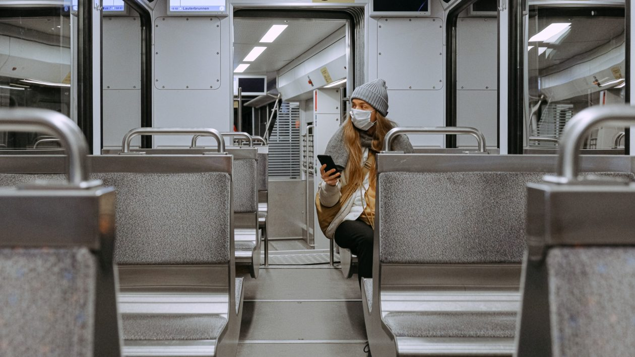 woman in a mask alone on a train accesses talkspace via her smart phone